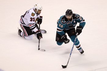SAN JOSE, CA - MAY 18:  Dan Boyle #22 of the San Jose Sharks moves the puck next to Dustin Byfuglien #33 of the Chicago Blackhawks in Game Two of the Western Conference Finals during the 2010 NHL Stanley Cup Playoffs at HP Pavilion on May 18, 2010 in San