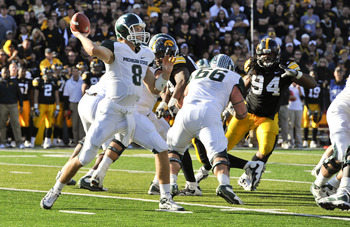 IOWA CITY, IA - OCTOBER 30- Quarterback Kirk Cousins #8 of the Michigan State Spartans throws under pressure from Defensive lineman Adrian Clayborn #94 of the University of Iowa Hawkeyes during the first half of play at Kinnick Stadium on October 30, 2010