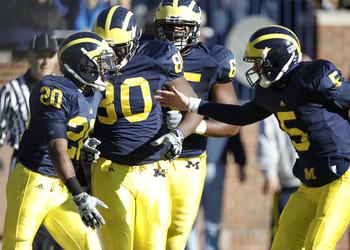 ANN ARBOR, MI - NOVEMBER 06:  Michael Shaw #20 of the Michigan Wolverines celebrates an overtime touchdown with Tate Forcier #5 and Martell Webb #80 while playing the Illinios Fighting Illini at Michigan Stadium on November 6, 2010 in Ann Arbor, Michigan.