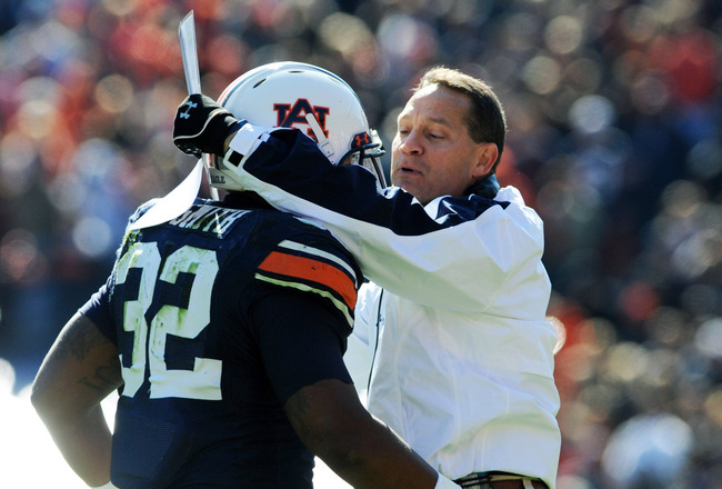 AUBURN, AL - NOVEMBER 6:  Coach Gene Chizik of the Auburn Tigers hugs running back Eric Smith #32 against the Chattanooga Mocs November 6, 2010 at Jordan-Hare Stadium in Auburn, Alabama.  (Photo by Al Messerschmidt/Getty Images)