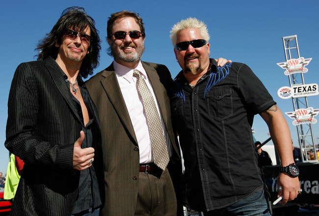 FORT WORTH, TX - NOVEMBER 07:  Lead singer of Foreigner Kelly Hansen, Texas Motor Speedway President Eddie Gossage and celebrity chef Guy Fieri pose during the NASCAR Sprint Cup Series AAA Texas 500 at Texas Motor Speedway on November 7, 2010 in Fort Wort