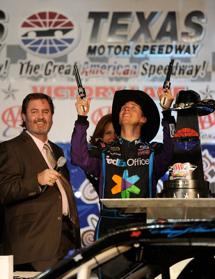 FORT WORTH, TX - NOVEMBER 07:  Texas Motor Speedway President Eddie Gossage (L) watches Denny Hamlin (C), driver of the #11 FedEx Office Toyota, as he shoots a Turnbull Revolvers in Victory Lane after winning the NASCAR Sprint Cup Series AAA Texas 500 at