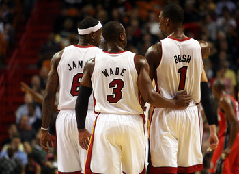 MIAMI - NOVEMBER 06: Dwyane Wade #3, LeBron James #6 and Chris Bosh #1 of the Miami Heat chat during a game against the New Jersey Nets  at American Airlines Arena on November 6, 2010 in Miami, Florida. NOTE TO USER: User expressly acknowledges and agrees