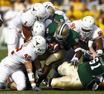 WACO, TX - NOVEMBER 14:  Running back Terrance Ganaway #24 of the Baylor Bears carries the ball against linebacker Dusting Earnest #42, linebacker Keenan Robinson #1, and tackle Kheeston Randall #91of the Texas Longhorns  during the second half on Novembe