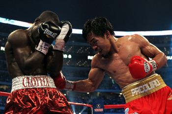 ARLINGTON, TX - MARCH 13:  (R-L) Manny Pacquiao of the Philippines throws a right to the body of Joshua Clottey of Ghana during the WBO welterweight title fight at Cowboys Stadium on March 13, 2010 in Arlington, Texas. Pacquiao defeated Clottey by unanimo