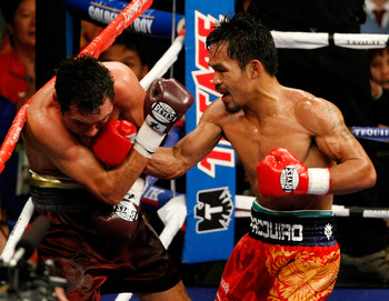 LAS VEGAS - DECEMBER 06:  (R-L) Manny Pacquiao of the Philippines connects with a right to the head of Oscar De La Hoya during their welterweight fight at the MGM Grand Garden Arena December 6, 2008 in Las Vegas, Nevada.  (Photo by Ethan Miller/Getty Imag