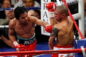 LAS VEGAS - NOVEMBER 14:  (L-R) Manny Pacquiao throws a left to the body of Miguel Cotto during their WBO welterweight title fight at the MGM Grand Garden Arena on November 14, 2009 in Las Vegas, Nevada. Pacquiao defeated Cotto by 12th round TKO.  (Photo