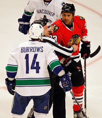 CHICAGO - MARCH 05: A referee tries to keep Dustin Byfuglien #33 of the Chicago Blackhawks away from Alexander Burrows #14 of the Vancouver Canucks at the United Center on March 5, 2010 in Chicago, Illinois. The Blackhawks defeated the Canucks 6-3. (Photo
