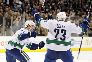 LOS ANGELES, CA - APRIL 21:  Henrik Sedin #33 of the Vancouver Canucks celebrates his go ahead goal with Alexander Edler #23 for a 5-4 lead over the Los Angeles Kings during the third period in game four of the Western Conference Quarter-final at Staples