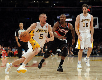 LOS ANGELES, CA - NOVEMBER 07:  Steve Blake #5 of the Los Angeles Lakers goes in for a layup past Armon Johnson #1 as Pau Gasol #16 looks on during the first half at the Staples Center on November 7, 2010 in Los Angeles, California.  NOTE TO USER: User ex