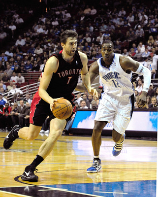 ORLANDO, FL - DECEMBER 16:  Andrea Bargnani #7 of the Toronto Raptors drives past Dwight Howard #12 of the Orlando Magic during the game at Amway Arena on December 16, 2009 in Orlando, Florida.  NOTE TO USER: User expressly acknowledges and agrees that, b