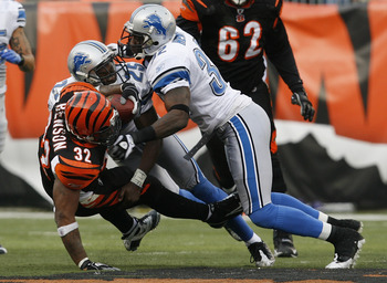 Bengals RB Cedric Benson is waylaid by two Detroit Lions tacklers