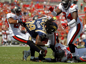 TAMPA, FL - OCTOBER 24:  Running back Steven Jackson #39 of the St. Louis Rams is tackled by defenders Ronde Barber #20, Sean Jones #26, Geno Hayes #54 and Kyle Moore #94 of the Tampa Bay Buccaneers during the game at Raymond James Stadium on October 24,