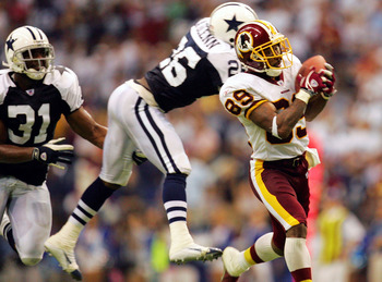 IRVING, TX - SEPTEMBER 19:  Wide receiver Santana Moss #89 of the Washington Redskins makes a pass reception and runs for a touchdown past Aaron Glenn #26 of the Dallas Cowboys on September 19, 2005 at Texas Stadium in Irving, Texas. The Redskins defeated