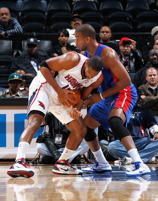 ATLANTA - NOVEMBER 03:  Al Horford #15 of the Atlanta Hawks looses grip on the ball as he drives into Greg Monroe #10 of the Detroit Pistons at Philips Arena on November 3, 2010 in Atlanta, Georgia.  NOTE TO USER: User expressly acknowledges and agrees th