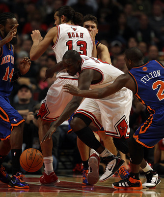 CHICAGO - NOVEMBER 04: Loul Deng #9 of the Chicago Bulls drives between teammate Joakim Noah #13 and Raymond Felton #2 of the New York Knicks at the United Center on November 4, 2010 in Chicago, Illinois. The Knicks defeated the Bulls 120-112. NOTE TO USE