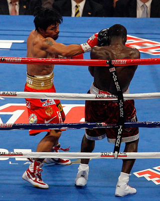 ARLINGTON, TX - MARCH 13:  (L-R) Manny Pacquiao of the Philippines throws a right to the head of Joshua Clottey of Ghana during the WBO welterweight title fight at Cowboys Stadium on March 13, 2010 in Arlington, Texas.  (Photo by Tom Pennington/Getty Imag