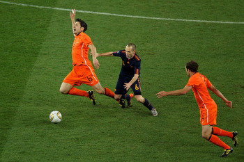 JOHANNESBURG, SOUTH AFRICA - JULY 11:  Mark Van Bommel of the Netherlands falls under the challenge of Andres Iniesta of Spain during the 2010 FIFA World Cup South Africa Final match between Netherlands and Spain at Soccer City Stadium on July 11, 2010 in