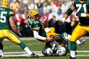 GREEN BAY, WI - OCTOBER 17: Aaron Rogers #12 of the Green Bay Packers is sacked by Cameron Wake #91 of the Miami Dolphins at Lambeau Field on October 17, 2010 in Green Bay, Wisconsin. (Photo by Scott Boehm/Getty Images)