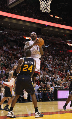 MIAMI - NOVEMBER 09:  Lebron James #6 of the Miami Heat drives to the hoop against Paul Millsap #24  during a game against the Utah Jazz at American Airlines Arena on November 9, 2010 in Miami, Florida. NOTE TO USER: User expressly acknowledges and agrees