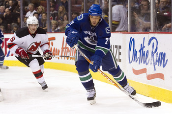 VANCOUVER, CANADA - NOVEMBER 1: Manny Malhotra #27 of the Vancouver Canucks makes a pass after getting past Andy Greene #6 of the New Jersey Devils during the second period in NHL action on November 01, 2010 at Rogers Arena in Vancouver, British Columbia,