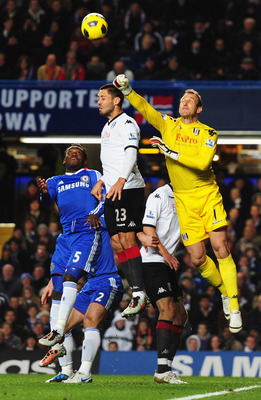 LONDON, ENGLAND - NOVEMBER 10:  Clint Dempsey (23) and Mark Schwarzer of Fulham foil Michael Essien of Chelsea during the Barclays Premier League match between Chelsea and Fulham at Stamford Bridge on November 10, 2010 in London, England.  (Photo by Mike