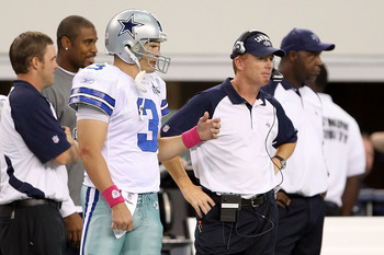 ARLINGTON, TX - OCTOBER 31:  (L-R) Quarterback Jon Kitna and assistant head coahc/offensive coordinator Jason Garrett of the Dallas Cowboys look on from the sideline against the Jacksonville Jaguars at Cowboys Stadium on October 31, 2010 in Arlington, Tex