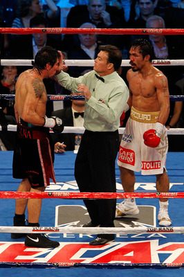ARLINGTON, TX - NOVEMBER 13:  Referee Laurence Cole inspects the cut on the eye of Antonio Margarito (black trunks) of Mexico as Manny Pacquiao (white trunks) of the Philippines looks on during their WBC World Super Welterweight Title bout at Cowboys Stad