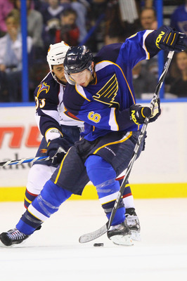 ST. LOUIS - OCTOBER 30: Erik Johnson #6 of the St. Louis Blues controls the puck against Dustin Byfuglien #33 of the Atlanta Thrashers at the Scottrade Center on October 30, 2010 in St. Louis, Missouri.  The Blues beat the Thrashers 4-3 in a shootout.  (P