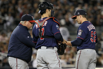 NEW YORK - OCTOBER 09:  Manager Ron Gardenhire #35 (L) takes starting pitcher Brian Duensing #52 of the Minnesota Twins out of the game in the bottom of the fourth inning against the New York Yankees during Game Three of the ALDS part of the 2010 MLB Play