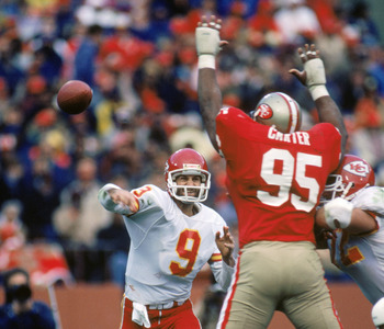 SAN FRANCISCO - NOVEMBER 17:  Quarterback Bill Kenney #9 of the Kansas City Chiefs attempts to pass over defensive linemen Michael Carter #95 of the San Francisco 49ers during a game at Candlestick Park on November 17, 1985 in San Francisco, California.