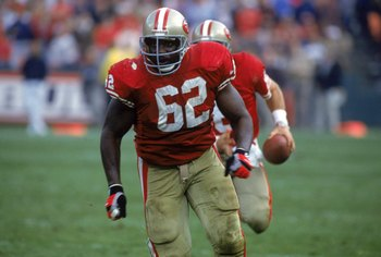 SAN FRANCISCO - NOVEMBER 15:  Guard Guy McIntyre #62 of the San Francisco 49ers is the lead blocker for running quarterback Steve Young #8 during a game against the New Orleans Saints at Candlestick Park on November 15, 1992 in San Francisco, California.