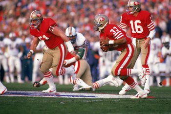 STANFORD, CA - JANUARY 20:  Running back Roger Craig #33 of the San Francisco 49ers follows his blocker offensive guard Randy Cross #51 in Super Bowl XIX against the Miami Dolphins at Stanford Stadium on January 20, 1985 in Stanford, California. The 49ers