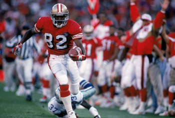 SAN FRANCISCO - NOVEMBER 13:  Wide receiver John Taylor #82 of the San Francisco 49ers runs with the ball during a game against the Dallas Cowboys at Candlestick Park on November 13, 1994 in San Francisco, California.  The 49ers won 21-14.  (Photo by Geor