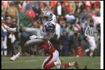 15 Jan 1995:  Wide receiver Michael Irvin of the Dallas Cowboys gets tackled by San Francisco 49ers defensive back Eric Davis during a playoff game at Candlestick Park in San Francisco, California.  The 49ers won the game, 38-28. Mandatory Credit: Otto Gr