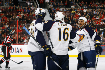 OTTAWA - NOVEMBER 09:  Andrew Ladd #16 of the Atlanta Thrashers celebrates his goal with teammates Nik Antropov #80 and Dustin Byfuglien #33 while Daniel Alfredsson #11 of the Ottawa Senators skates away dejectedly during a game at Scotiabank Place on Nov