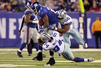 EAST RUTHERFORD, NJ - NOVEMBER 14: Bradie James #56 and DeMarcus Ware #94 of the Dallas Cowboys combine to stop a run by Brandon Jacobs #27 of the New York Giants on November 14, 2010 at the New Meadowlands Stadium in East Rutherford, New Jersey. The Cowb
