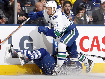 TORONTO - NOVEMBER 13: Mikhail Grabovski #84 of the Toronto Maple Leafs gets run over by Manny Malhotra #27 of the Vancouver Canucks during game action at the Air Canada Centre November 13, 2010 in Toronto, Ontario, Canada. (Photo by Abelimages / Getty Im