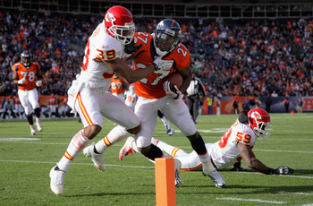DENVER - NOVEMBER 14:  Running back Knowshon Moreno #27 of the Denver Broncos makes a 17 yard pass reception and fights his way past cornerback Brandon Carr #39 of the Kansas City Chiefs for a first quarter touchdown at INVESCO Field at Mile High on Novem