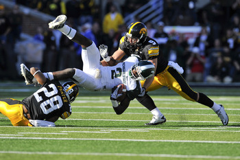 IOWA CITY, IA - OCTOBER 30: Wide receiver Mark Bell #2 of the Michigan State Spartans is tackled by defensive back Tyler Sash #9 of the University of Iowa Hawkeyes and his teammate defensive back Shaun Prater #28 as he rushes for yards during the first ha
