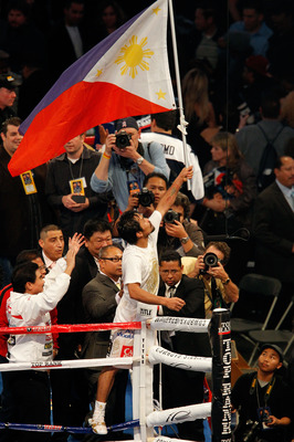 ARLINGTON, TX - NOVEMBER 13:  Manny Pacquiao (white trunks) of the Philippines celebrates after he was declared the winner by a unanimous decision against Antonio Margarito (black trunks) of Mexico during their WBC World Super Welterweight Title bout at C