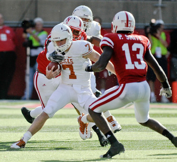 LINCOLN, NE - OCTOBER 16: Quarterback Garrett Gilbert #7 of the Texas Longhorns tries to avoid safety P.J. Smith #13 and Nebraska Cornhuskers during second half action of their game at Memorial Stadium on October 16, 2010 in Lincoln, Nebraska. Texas Defea