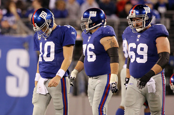 EAST RUTHERFORD, NJ - NOVEMBER 14:  Chris Snee #76, Eli Manning #10, and Rich Seubert #69 of the New York Giants walk off the field after losing the ball on a fumble in the fourth quarter against of the Dallas Cowboys on November 14, 2010 at the New Meado