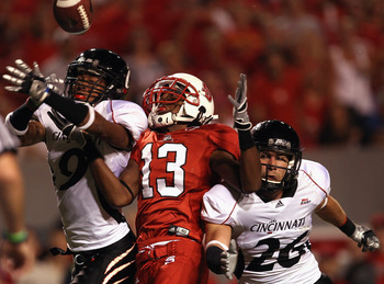 RALEIGH, NC - SEPTEMBER 16:  Teammates Dominique Battle #9 and Drew Frey #26 of the Cincinnati Bearcats break up a pass to Owen Spencer #13 of the North Carolina State Wolfpack during their game at Carter-Finley Stadium on September 16, 2010 in Raleigh, N