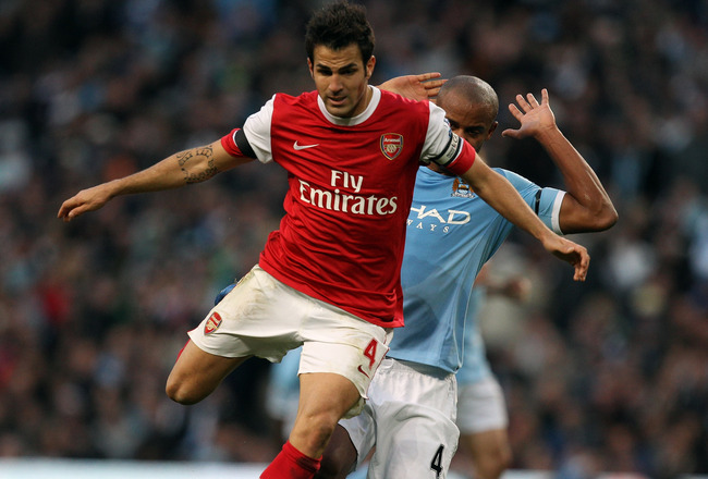 MANCHESTER, ENGLAND - OCTOBER 24:  Cesc Fabregas of Arsenal holds off Vincent Kompany of City during the Barclays Premier League match between Manchester City and Arsenal at City of Manchester Stadium on October 24, 2010 in Manchester, England.  (Photo by