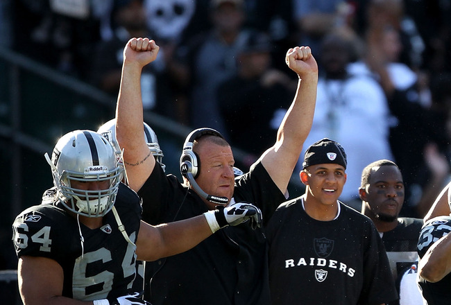 OAKLAND, CA - OCTOBER 31: Head coach Tom Cable of the Oakland Raiders celebrates with his arms in the air while Tyvon Branch #33 runs back an interception against the Seattle Seahawks at Oakland-Alameda County Coliseum on October 31, 2010 in Oakland, Cali