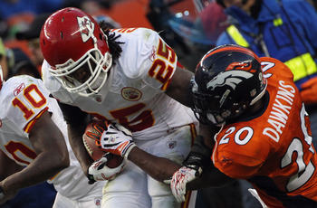 DENVER - NOVEMBER 14:  Running back Jamaal Charles #25 of the Kansas City Chiefs rushes as Brian Dawkins #20 of the Denver Broncos tries to strip the ball at INVESCO Field at Mile High on November 14, 2010 in Denver, Colorado. The Broncos defeated the Chi