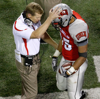 LAS VEGAS - NOVEMBER 13:  Head coach Bobby Hauck of the UNLV Rebels congratulates Tim Cornett #35 after he scored his fourth touchdown against the Wyoming Cowboys at Sam Boyd Stadium November 13, 2010 in Las Vegas, Nevada. UNLV won 42-16.  (Photo by Ethan