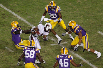 BATON ROUGE, LA - NOVEMBER 13:  Jyruss Edwards #7 of the University of Louisiana-Monroe Warhawks avoids is tackled by Craig Loston #6 of the Louisiana State University Tigers at Tiger Stadium on November 13, 2010 in Baton Rouge, Louisiana.  The Tigers def