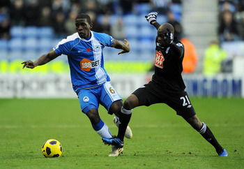 WIGAN, ENGLAND - NOVEMBER 13:  Hendry Thomas of Wigan Athletic is challenged by Youssuf Mulumbu of West Bromwich Albion during the Barclays Premier League match between Wigan Athletic and West Bromwich Albion at DW Stadium on November 13, 2010 in Wigan, E